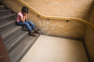 teenage african american girl crying on staircase at school, sitting on step